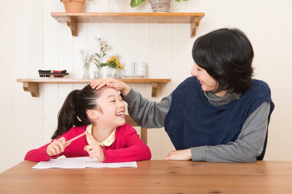勉強をする娘を褒める母親