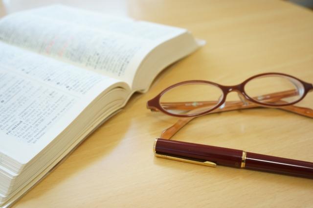 英語の辞書と眼鏡とペン