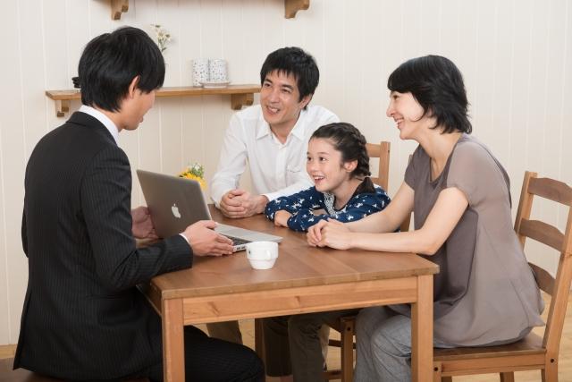 パソコンで営業マンの説明を受ける家族