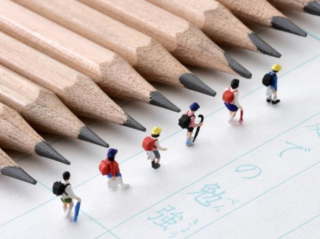 鉛筆とノートの上を並んで歩く小学生の人形
