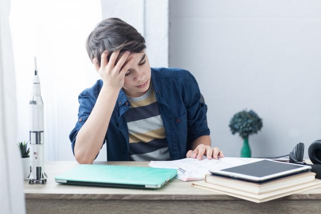 勉強しながら思い悩む青年